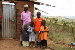 Peter's moeder voor de deur van hun nieuwe, zelfgebouwde huis met een paar van de kinderen, Mithini Ithanga, Kenia