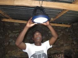 De solar lamp wordt een de dragende balken van het dak bevestigd, Baringo, Donyo Sabuk area, Kenya