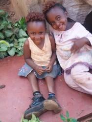 Akoth (Dedii-6) met haar zusje op de grond voor hun huisje, medische zorg, special need child, Circle4life CBO, Circle4life