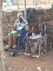 Francis in zijn nieuwe rolstoel, de oude staat er naast. Family empowerment, crisis aid, Kenia