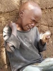 Pius met een biscuitje bij het huis in Maendeleo, Circle4life crisis aid, family empowerment, education