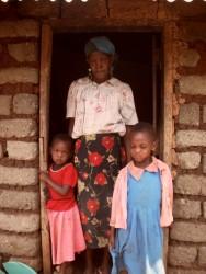 Jackline en Ruth samen met oma in de deuropening van het huisje in Mithini, Kenia
