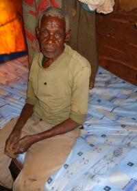Waweru op het bed met de nieuwe matras, Gatanga, Kenya