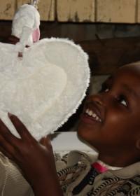 Een van de zusjes uit Korogocho met een Happy Horse muziekdoos in de vorm van een zwaan