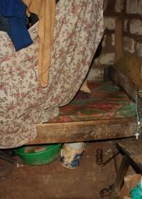 De binnenkant van het huisje waar de vader en drie kinderen in een bed slapen. Het dak staat op instorten en vertoont grote gaten.Park Village,Kenia