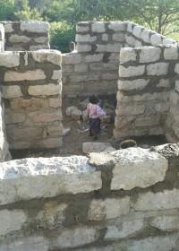 Het kleine broertje van Onesmus kijkt verbaasd naar het huis in aanbouw, Uamani, Kenia