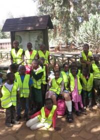 Groepsfoto voor de ingang van de Orphanage, National Park Nairobi, KWS