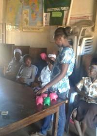 Maatschappelijk werkster Margarete Njeri legt het doel van de spaarvarkentjes uit, family empowerment, energiezuinige jiko, Circle4life Kenia, Wisdom Stoves Org.