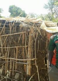 Kennedy voor zijn hutje in Baringo, tijd voor actie en een huisje voor hem te bouwen, family empowerment, crisis aid, Circle4life Kenya