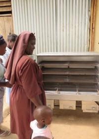 De huismoeders en zuster kijken vol belangstelling naar de nieuwe oven, Makongoni, Kenia