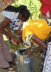 Het aansteken van de Wisdom Stove, Catherine en maatschappelijk werkster Margarete Njeri, Circle4life Kenya