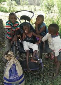Gehandicapte Paul en zijn broertje en zusje zijn blij maatschappelijk werkster Margarete Njeri te zien, family empowerment, Kenya, Ndulya