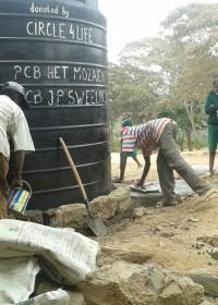 Tank op zijn plaatst, ondergrondse waterput met kraan en nu de rand om de tank, Circle4life Kenya, Education, family empowerment