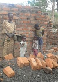 Crisis hulp, Circle4life Kenya, Pauline met een paar van haar kinderen voor het huis in aanbouw