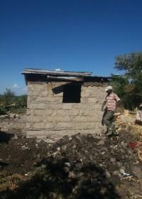 De fundi legt de laatste hand aan de buitenkant van het nieuwe huis, Baringo, Kenia, Circle4life