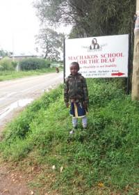 Eunice (5) voor de ingang van Machakos School for the Deaf, haar nieuwe school vanaf januari 2019, Circle4life Kenya, special need children
