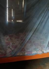 Een bed in een nieuw huis, met matras, lakens, deken en klamboe, family empowerment Circle4life Kenia