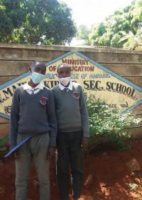 Julius en Josphat voor de ingang van de school, opnieuw opgenomen in het programma van Circle4life, Kiboko, Kenya