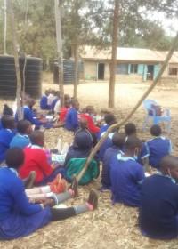 Voorlichting in het grasveld op het schoolterrein, Uamani Primary School, Circle4life