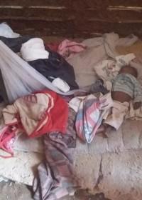 De baby slaapt op oude kleren op een vochtige kleigrond, Circle4life Kenia, crisishulp, home construction